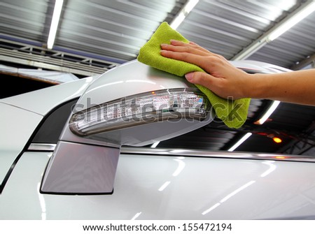 Hand with a wipe the car side mirror polishing car wash - stock photo