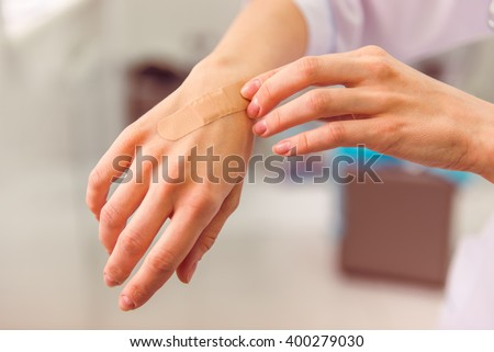 Hand with adhesive plaster that covering a slight injury, close-up - stock photo