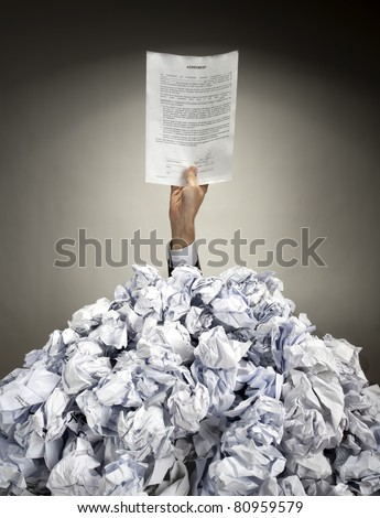Hand with Agreement reaches out from big heap of crumpled papers