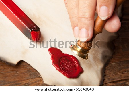 Hand with ancient parchment or diploma scroll with wax seal
