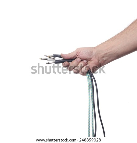 Hand with audio cable isolated on white background - stock photo