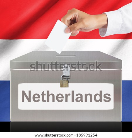 Hand with ballot and metal box with Netherlands flag, elections and democracy concept - stock photo