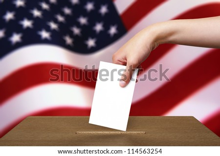 Hand with ballot and wooden box on Flag of USA - stock photo