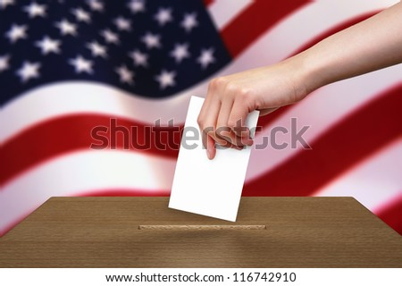Hand with ballot and wooden box on Flag of USA