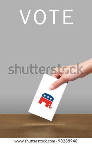 Hand with ballot and wooden box with Republican party icon - stock photo