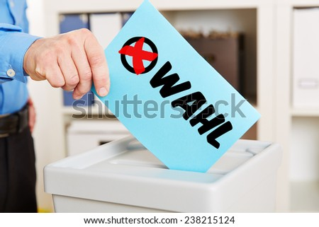 Hand with ballot paper on ballot box during election - stock photo
