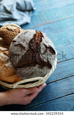 hand with basket full of breads, baking - stock photo