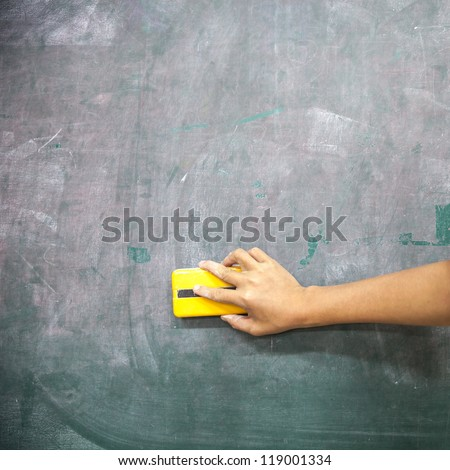 hand with blackboard eraser cleaning blackboard - stock photo