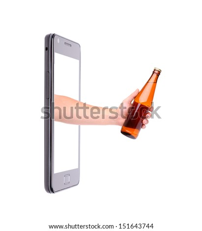 Hand with bottle of beer climbs from phone. - stock photo