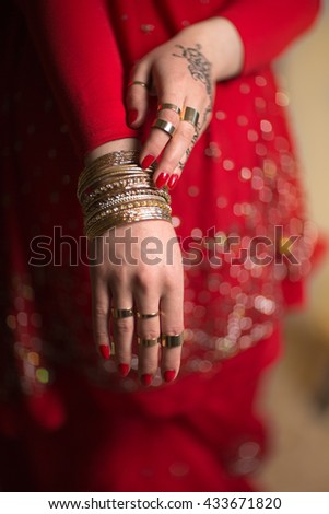 Hand with bracelets Indian woman in red saree. Mehendi. Saree. India. - stock photo