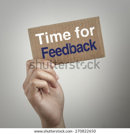 Hand with brown card is showing Time for feedback with gray background. - stock photo