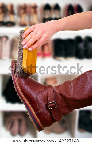hand with brush cleaning brown leather boot - stock photo