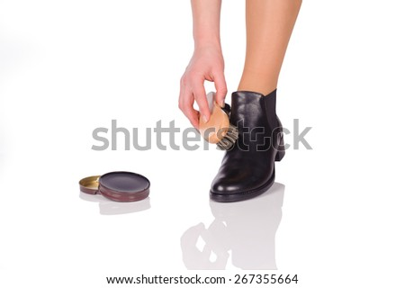 Hand with brush cleaning shoes, isolated on white - stock photo