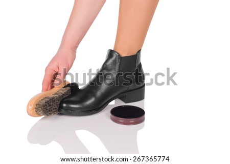 Hand with brush cleaning shoes, isolated on white