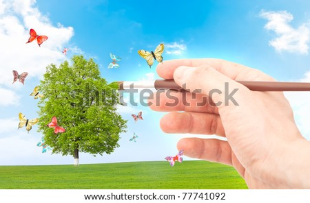 Hand with brush painting natural image. Spring and summer concept. - stock photo