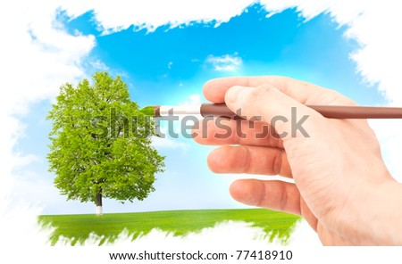 Hand with brush painting natural image. Spring concept. - stock photo