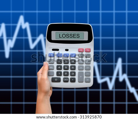 Hand with calculator in the background business graph showing lose. - stock photo