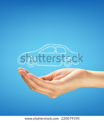 Hand with car against blue background. - stock photo