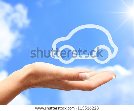 Hand with car against blue sky background - stock photo