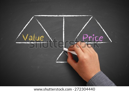 Hand with chalk is drawing Value and price balance scale on the chalkboard. - stock photo