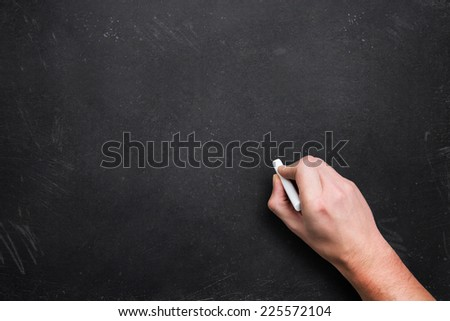 hand with chalk, starting to write  - stock photo