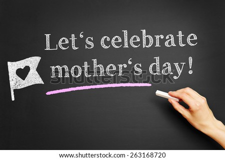 "Hand with chalk writing ""Let's celebrate mother's day!"" on a blackboard - stock photo"
