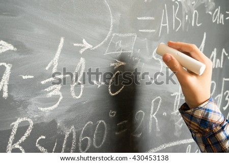 Hand with chalk writting on math formulas black board - stock photo