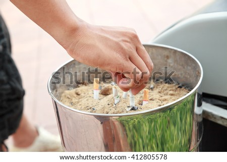 Hand with cigarette butt and ashtray. - stock photo