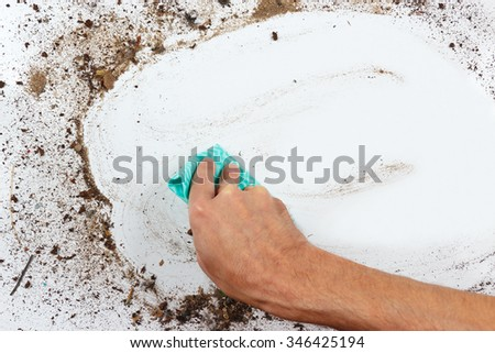 Hand with cloth cleans a dirty surface - stock photo