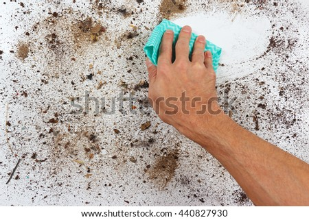 Hand with cloth wiping a dirty surface - stock photo