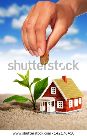 Hand with coin and house. - stock photo