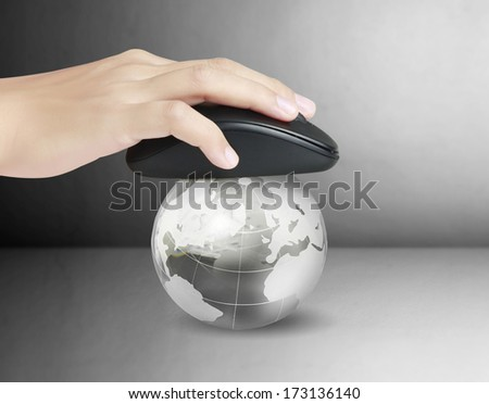Hand with computer mouse and a globe - stock photo