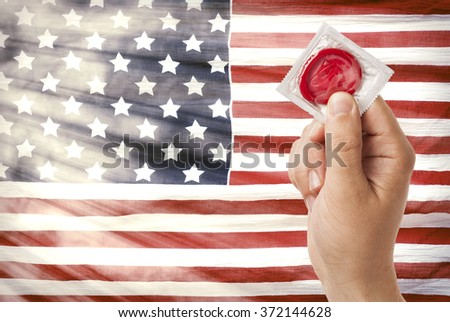 Hand with condom - stock photo