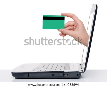 hand with credit card comes from laptop screen - stock photo