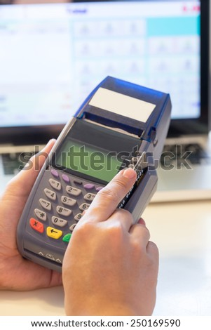 Hand With Credit Card Swipe Through Terminal For Sale In Store - stock photo
