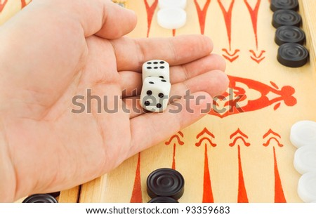 Hand with dices and backgammon game - stock photo