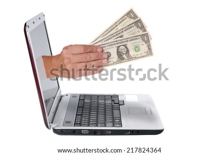 Hand with dollar banknotes comes from the laptop screen  - stock photo