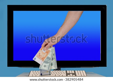 hand with dollars and euros out of the monitor. Next to keyboard.