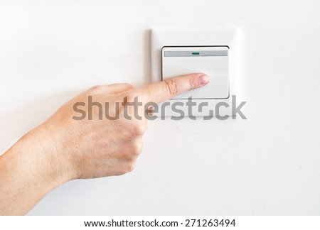 Hand with finger on light switch - stock photo