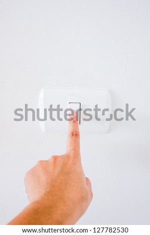 hand with finger on light switch, about to turn off the lights. - stock photo