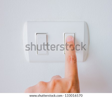 hand with finger on light switch, about to turn on the lights. - stock photo