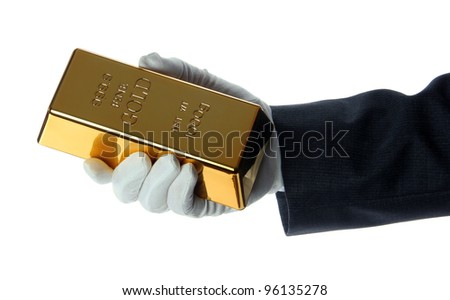 hand with glove holding a gold bullion