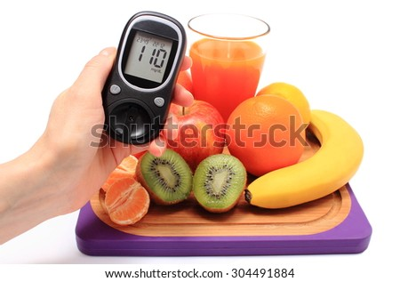 Hand with glucometer, fresh ripe natural fruits and glass of juice on cutting board, concept for diabetes, healthy nutrition and strengthening immunity - stock photo