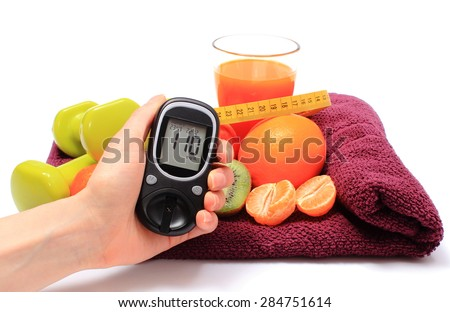Hand with glucose meter, fresh fruits with tape measure, glass of juice and green dumbbells for fitness, concept for diabetes, slimming, healthy nutrition and strengthening immunity