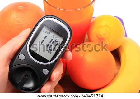 Hand with glucose meter, fresh ripe natural fruits and glass of juice, concept for diabetes, healthy nutrition and strengthening immunity