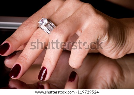 Hand with golden jewelry on black background - stock photo