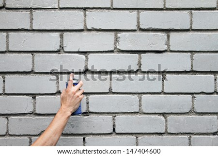 hand with graffiti spray can in front of a blank brick wall - stock photo