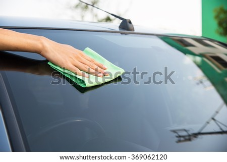 Hand with green microfiber cloth, cleaning glass car. - stock photo