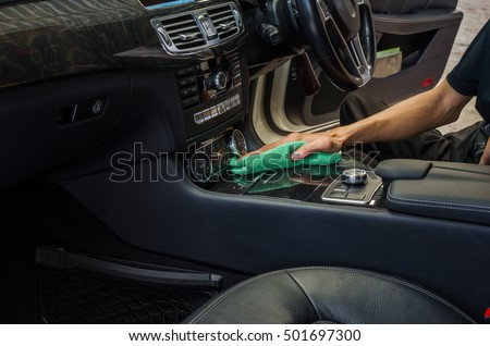 Hand with green microfiber cloth cleaning interior car.