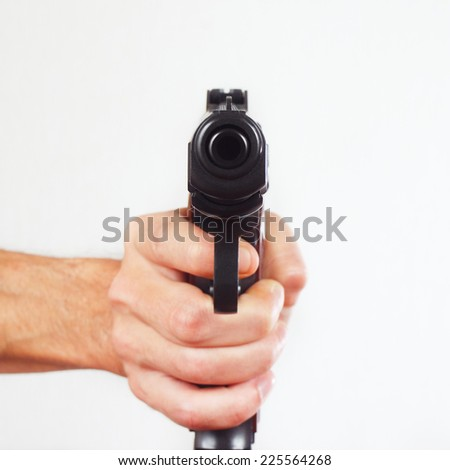 Hand with gun pointing forward close up - stock photo